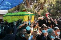 Women throw rose petals at the coffin of Mohamed Tahan, who was killed at the border fence with Israel yesterday, during his funeral in Adloun
