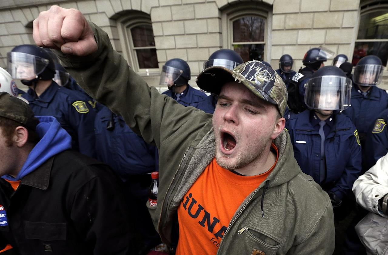 Drew Dobson, of Coleman, Mich., protests at a rally at the State Capitol in Lansing, Mich., Tuesday, Dec. 11, 2012. The crowd is protesting right-to-work legislation passed last week. Michigan could become the 24th state with a right-to-work law next week. Rules required a five-day wait before the House and Senate vote on each other's bills; lawmakers are scheduled to reconvene Tuesday and Gov. Snyder has pledged to sign the bills into law. (AP Photo/Paul Sancya)p