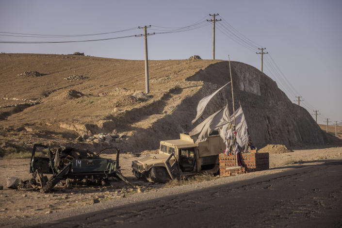 A destroyed Afghan police pickup and Humvee next to a grave along Highway 1 just outside Kabul, Afghanistan, Sept. 9, 2021. (Jim Huylebroek/The New York Times)