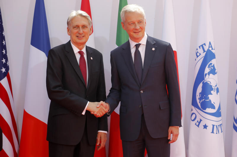French Finance Minister Bruno Le Maire, right, welcomes British Chancellor of the Exchequer Philip Hammond at the G-7 Finance Wednesday July 17, 2019.The top finance officials of the Group of Seven rich democracies are arriving at Chantilly, at the start of a two-day meeting aimed at finding common ground on how to tax technology companies and on the risk from new digital currencies. (AP Photo/Michel Euler)