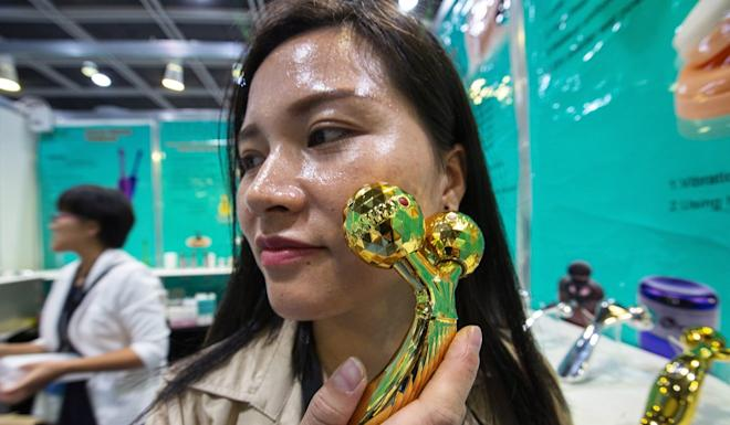 An exhibitor from China demonstrates an electronic vibrating face massager at the Hong Kong Electronics Fair (Autumn Edition) in 2018. Photo: EPA-EFE