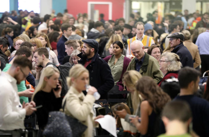 Passengers at Gatwick airport waiting for their flights following the delays and cancellations brought on by drone sightings near the airfield, in London, Friday Dec. 21, 2018. New drone sightings Friday caused fresh chaos for holiday travelers at London's Gatwick Airport. (John Stillwell/PA via AP)