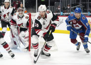 Arizona Coyotes defenseman Jason Demers, center, clears the puck from the net guarded by goaltender Ivan Prosvetov, left, as Colorado Avalanche left wing Andre Burakovsky trails the play in the second period of an NHL hockey game Monday, April 12, 2021, in Denver. (AP Photo/David Zalubowski)