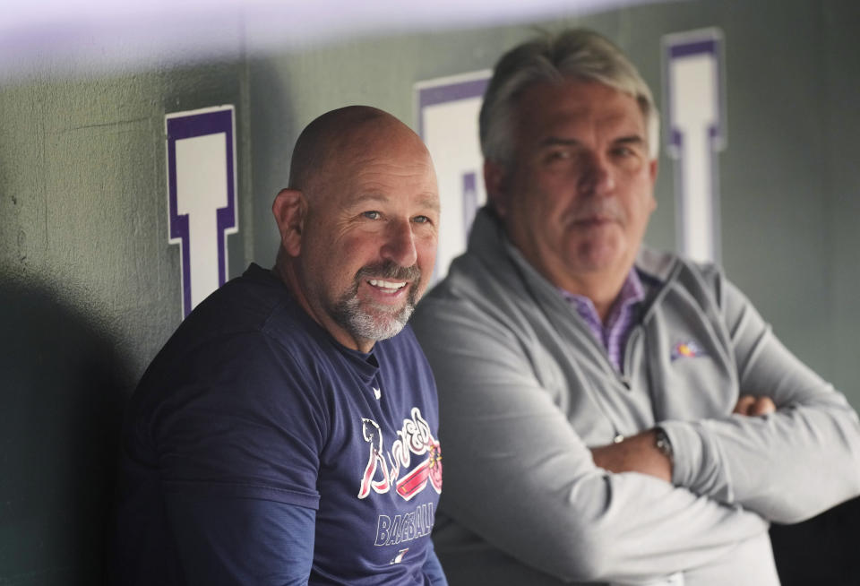 Atlanta Braves bench coach Walt Weiss, front, jokes with Colorado Rockies interim general manager Bill Schmidt as players warm up for a baseball game Thursday, Sept. 2, 2021, in Denver. (AP Photo/David Zalubowski)