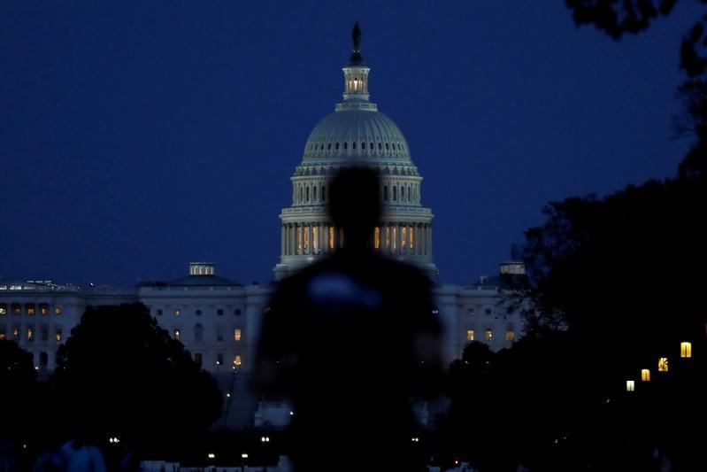 People walk past the U.S. Capitol Building in Washington