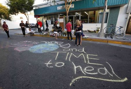 """Women hug next to a chalk message that reads """"World give us love and time to heal"""" outside a deli that was one of nine crime scenes after series of drive-by shootings that left 7 people dead in the Isla Vista neighborhood of Santa Barbara, California May 26, 2014. REUTERS/Lucy Nicholson"""
