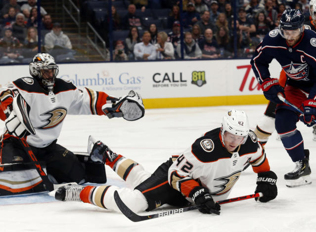 Anaheim Ducks defenseman Josh Manson, center, tries to control the puck in front of Ducks goalie Ryan Miller, left, and Columbus Blue Jackets forward Nick Foligno during the second period of an NHL hockey game in Columbus, Ohio, Friday, Oct. 11, 2019. (AP Photo/Paul Vernon)
