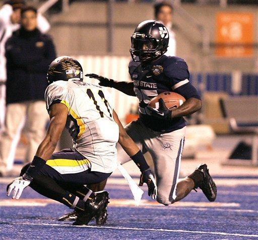 Utah State's Kerwynn Williams (25) rushes for a first down against Toledo's Cheatham Norrils (11) during the second half of an NCAA college football game on Saturday, Dec. 15, 2012, in Boise, Idaho. Utah State went on to win the Famous Idaho Potato Bowl game 41-15. (AP Photo/Matt Cilley)
