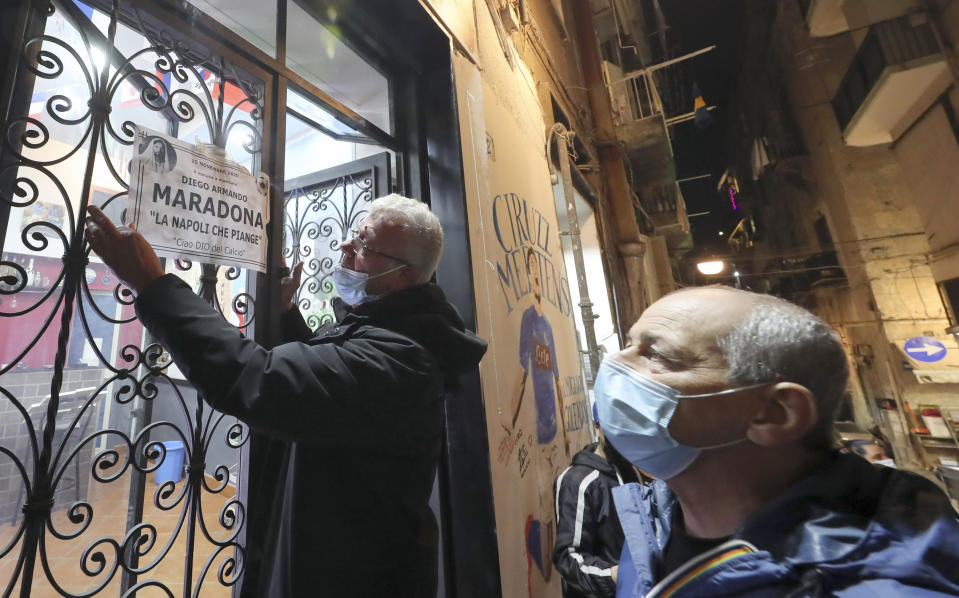 "A man sticks an obituary reading in Italian ""Maradona, Naples who cries, Ciao god of soccer"", in Naples, Italy, Wednesday, Nov. 25, 2020. Diego Maradona has died. The Argentine soccer great was among the best players ever and who led his country to the 1986 World Cup title before later struggling with cocaine use and obesity. He was 60. (AP Photo/Salvatore Laporta)"