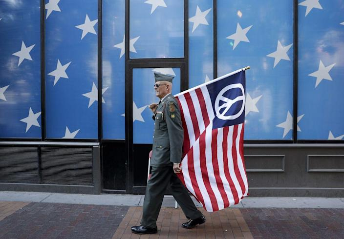 <p>A protester carrying a peace flag walks in downtown Cleveland, Ohio, on July 17, 2016, in preparation for the Republican National Convention. (Photo: Patrick Semansky/AP)</p><p><br></p>