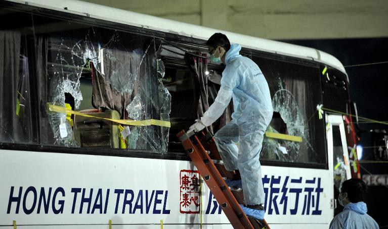 Members of a Hong Kong police forensic team examine the tourist bus used in the Manila bus hijacking in which eight Hong Kong tourists died on August 23, 2010