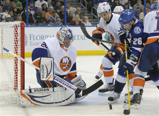 New York Islanders goalie Evgeni Nabokov, left, of Kazakhstan, and New York Islanders center Frans Nielsen, center, of Denmark, defend against a shot on-goal by Tampa Bay Lightning right wing Martin St. Louis, right, during the second period of an NHL hockey game on Thursday, March 14, 2013, in Tampa, Fla. (AP Photo/Brian Blanco)