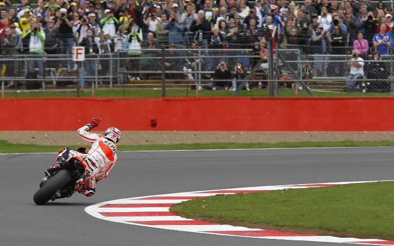 Repsol Honda's Spanish rider Marc Marquez acknowledges the crowd at the end of the qualifying session for the British MotoGP at Silverstone in Northamptonshire, central England, on August 30, 2014