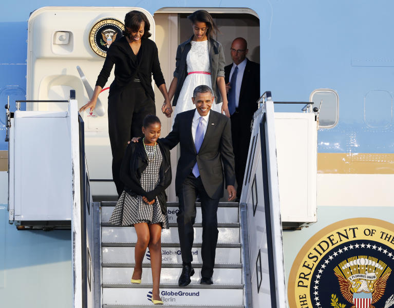 FILE - In this June 18, 2013, file photo, US President Barack Obama and first lady Michelle Obama and their daughters Sasha, left, and Malia disembark from Air Force One at the Tegel airport in Berlin. The man who lives at 1600 Pennsylvania Ave. is more than just another famous face, or the face behind the government's troubled health care website. Five new things about the president include, singing in the bathroom, cooking, a broken nose, a world traveler and a daughter with a peanut allergy. (AP Photo/Michael Probst, File)