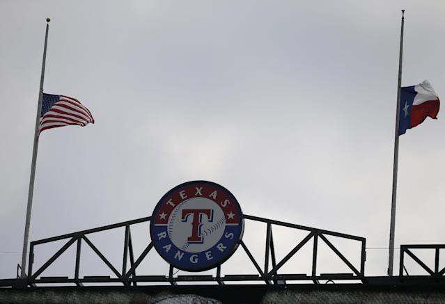 The United States, left, and Texas flags wave in the breeze at half staff, in honor of the 12th anniversary of the Sept. 11 terrorist attacks, during the first inning of a baseball game betwen the Pittsburgh Pirates and Texas Rangers Wednesday, Sept. 11, 2013, in Arlington, Texas. (AP Photo/Tony Gutierrez)