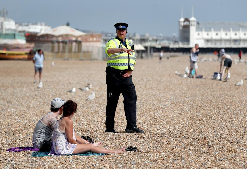 A police officer advises people to leave the beach during the warm weather in Brighton as the UK continues in lockdown to help curb the spread of the coronavirus.