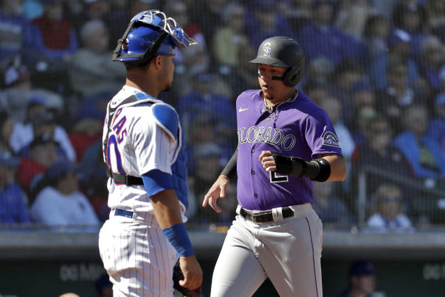 Colorado Rockies' Yonathan Daza scores on a double hit by teammate Drew Butera during the second inning of a spring training baseball game as Chicago Cubs catcher Willson Contreras looks on, Tuesday, Feb. 25, 2020, in Mesa, Ariz. (AP Photo/Matt York)
