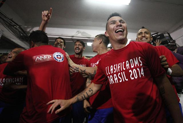 Chile players celebrate after their 2014 World Cup qualifying soccer match against Ecuador, in Santiago, Chile, Tuesday, Oct. 15, 2013. Chile and Ecuador booked their World Cup place in Brazil 2014. Chile won 2-1. (AP Photo/Luis Hidalgo)