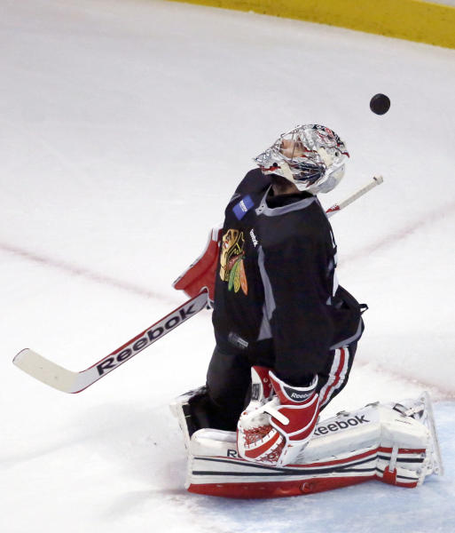 Chicago Blackhawks goalie Corey Crawford keeps his eyes on the puck during NHL hockey practice, Tuesday, June 11, 2013 in Chicago. The Blackhawks host the Boston Bruins in Game 1 of the Stanley Cup finals on Wednesday. (AP Photo/Charles Rex Arbogast)