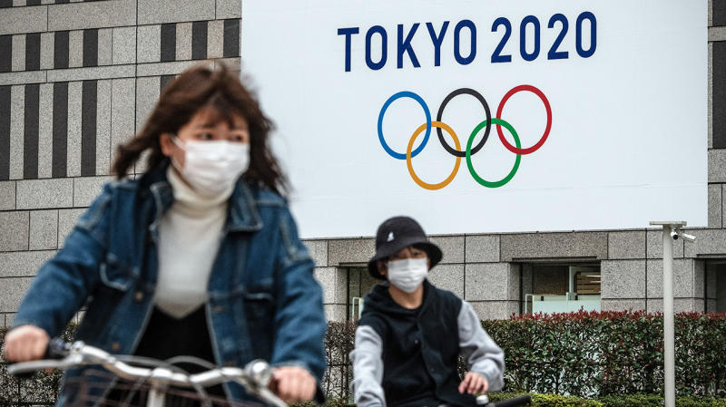 People ride past a banner for the Tokyo Olympics with masks.