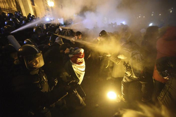 """Protesters clash with police during a demonstration against the amendments to the labour code, dubbed """"slave law"""" by oppositional forces, at the parliament building in Budapest, Thursday, Dec. 13, 2018. Thursday's evening rally was called to oppose recent changes to the labor code which unions and critics say will hurt workers and protesters shouted slogans against Prime Minister Viktor Orban. Some protesters threw bottles and smoke bombs at police in riot gear guarding the neo-Gothic national legislature.(Zoltan Balogh/MTI via AP)"""