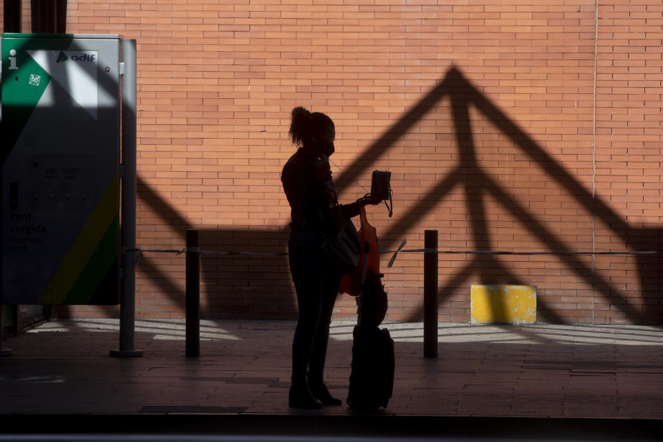 A passenger stands outside Atocha rail station after arriving by taxi in Madrid, Spain, Saturday, Oct. 3, 2020. Madrid has started its first day under a partial lockdown with police controlling travel in and out of the Spanish capital. Spain's largest city has become the continent's biggest hot spot for the second wave of the coronavirus. The measures, affecting 4.8 million people, prohibit all nonessential trips in and out of the capital and nine of its suburbs. (AP Photo/Paul White)