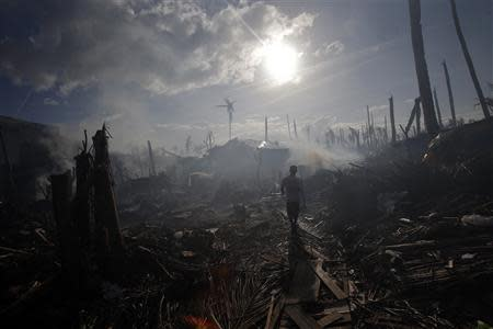 A man walks through smoke from fires in a part of Tolosa devastated by Typhoon Haiyan, November 16, 2013. Long-delayed emergency supplies flowed into the typhoon-ravaged central Philippines on Saturday, reaching desperate families who had to fend for themselves for days, as the United Nations more than doubled its estimate of homeless to nearly two million. REUTERS/John Javellana