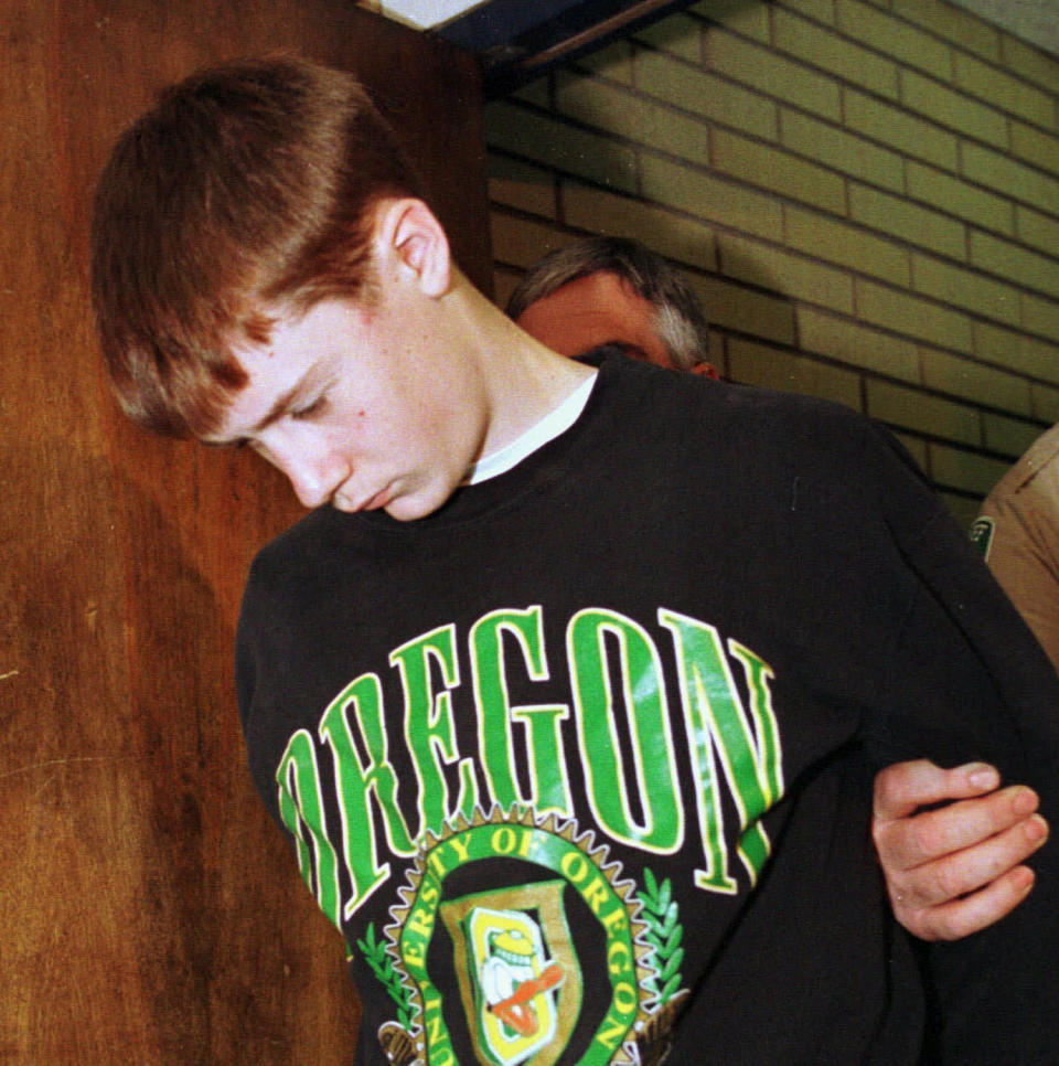 """FILE - In this May 22, 1998, file photo, Thurston High School student Kip Kinkel, 15, is led to his arraignment in Eugene, Ore. Kip Kinkel, who killed his parents before going on a shooting rampage at his Oregon high school in 1998, killing two classmates and injuring 25 more, has given his first news interview, telling HuffPost he feels """"tremendous, tremendous shame and guilt.""""(AP Photo/Don Ryan, File)"""