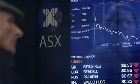 A man looks the board of the Australian Securities Exchange in Sydney