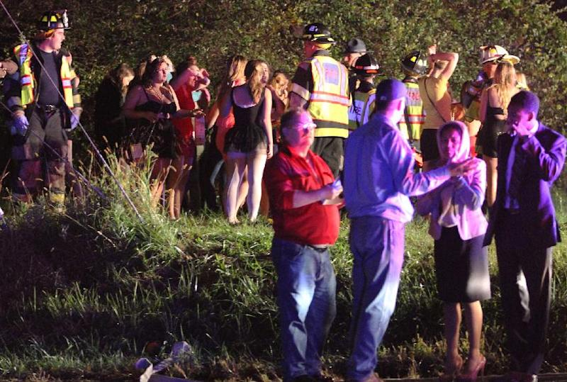 Passengers congregate on the roadside after a bus overturned on Howell School Road after colliding with a car carrier truck at the intersection with Summit Bridge Road, reported about 10:00 p.m. Thursday evening, Oct. 10, 2013. In a news release, state police Cpl. John Day says about 40 young adults, ages 18 to 22, were on the bus at the time. (AP Photo/The News Journal, William Bretzger)