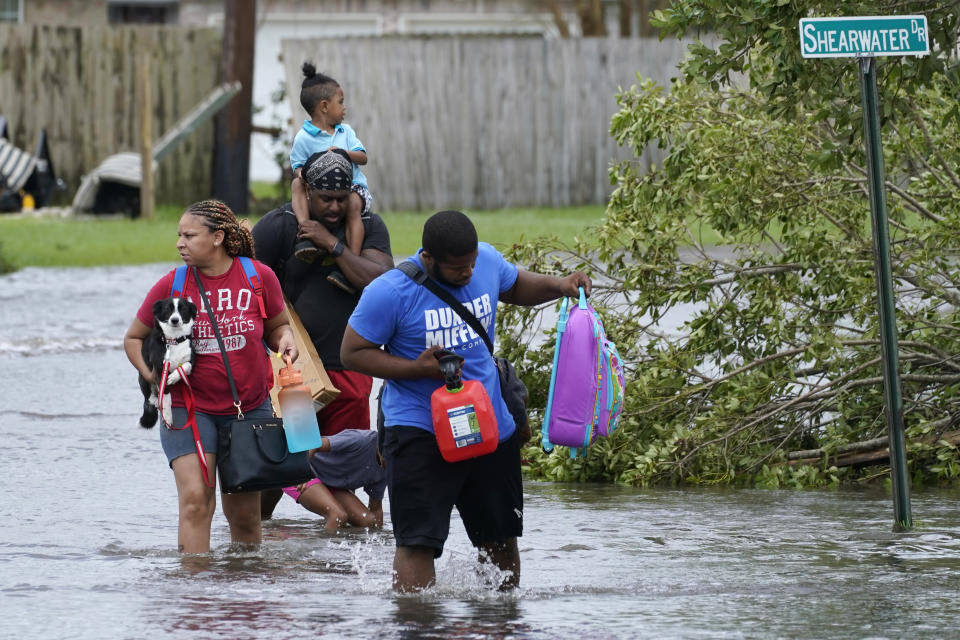 Michael Thomas, back, carries his daughter Mikala, out of his flooded neighborhood after Hurricane Ida moved through Monday, Aug. 30, 2021, in LaPlace, La. (AP Photo/Steve Helber)