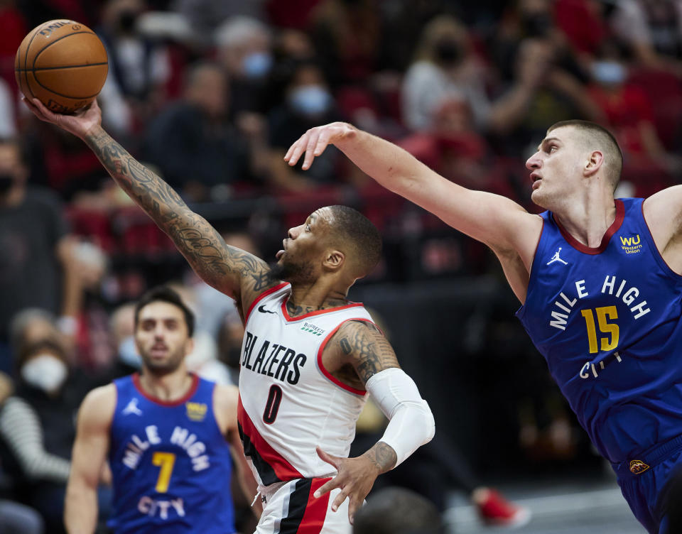 Portland Trail Blazers guard Damian Lillard shoots in front of Denver Nuggets center Nikola Jokic, right, during the second half of Game 3 of an NBA basketball first-round playoff series Thursday, May 27, 2021, in Portland, Ore. (AP Photo/Craig Mitchelldyer)