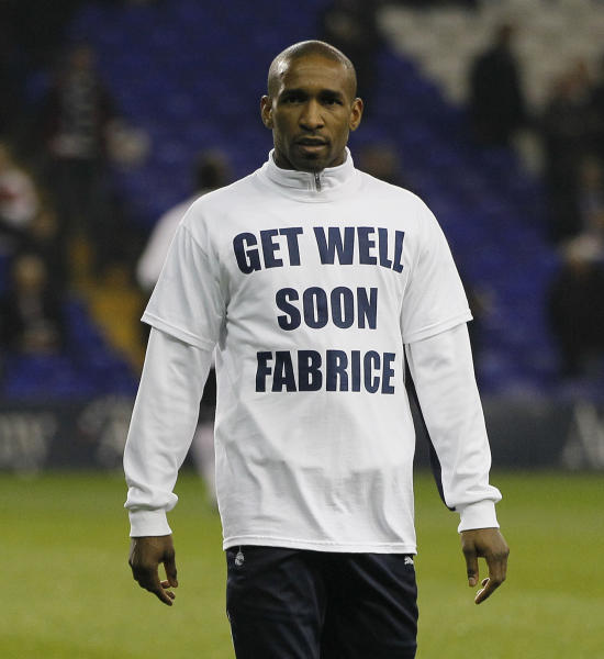 Tottenham Hotspur's Jermain Defoe wears a get well soon Fabrice T-shirt as he warms up prior to playing against Stoke City during their English Premier League soccer match at Tottenham's White hart Lane stadium in London, Wednesday, March, 21, 2012. The T shirt is for Fabrice Muamba who suffered a heart attack while playing against Tottenham Hotspur for Bolton Wanderers on Saturday March 17.(AP Photo/Alastair Grant)