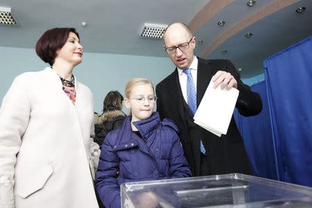 Ukraine's Prime Minister Arseny Yatseniuk casts his ballot, as his daughter Sofiya and wife Teresiya stand nearby, during a parliamentary election at a polling station in Kiev, October 26, 2014. REUTERS/Valentyn Ogirenko