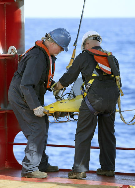 In this April 4, 2014, photo provided by the Australian Defense Force, Mike Unzicker, left, and Chris Minor deploy the towed pinger locator off the deck of Australian Defense vessel Ocean Shield in the first search for the missing flight data recorder and cockpit voice recorder in the southern Indian Ocean. Ocean Shield, which is carrying high-tech sound detectors from the U.S. Navy, was investigating a sound it picked up. (AP Photo/Australian Defense Force, Lt. Kelly Lunt) EDITORIAL USE ONLY