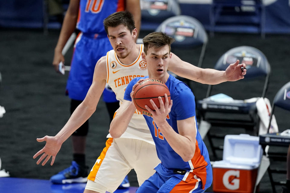 Florida's Colin Castleton, right, is defended by Tennessee's John Fulkerson, left, in the first half of an NCAA college basketball game in the Southeastern Conference Tournament Friday, March 12, 2021, in Nashville, Tenn. (AP Photo/Mark Humphrey)