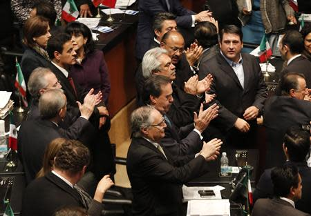 Senators of the ruling PRI applaud after Mexico's Senate signed off on an energy bill at the Senate building in Mexico City