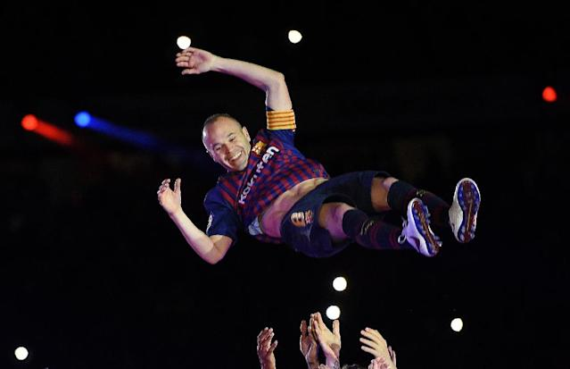 Japan bound: Andres Iniesta is thrown in the air by Barcelona teammates at his last match for the club at the weekend (AFP Photo/LLUIS GENE )