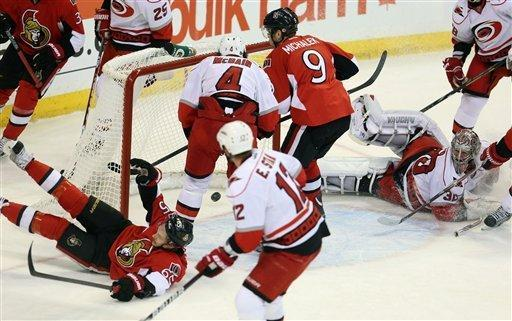 Ottawa Senators' Erik Karlsson (65)) falls as he celebrates his goal as Carolina Hurricanes goaltender Cam Ward (30) looks back into his net during first-period NHL hockey game action in Ottawa, Thursday, Feb. 7, 2013. (AP Photo/The Canadian Press, Fred Chartrand)