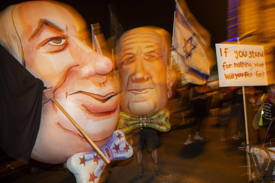 "FILE - In this Saturday, Aug. 8, 2020 file photo, demonstrators wear mask depicting Israel's Prime Minister Benjamin Netanyahu, left, and Defense Minister and coalition partner Benny Gantz, right, during a protest in Jerusalem, Israel. When Netanyahu and his rival, Gantz, agreed to form an ""emergency"" government in May after three bitter, and ultimately deadlocked, election campaigns, the goal was to stabilize Israeli politics in the face of a global pandemic. Less than 100 days later their fractious coalition government appears to be headed toward collapse as Israel grapples with a raging coronavirus outbreak, an economic calamity and a wave of public protests. (AP Photo/Ariel Schalit, File)"