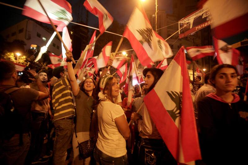 Lebanese anti-government protesters wave national flags and chant slogans in Sassine Square, just steps away from the site where Brig. Gen. Wissam al-Hassan was assassinated Friday in a car bomb attack, in Beirut, Lebanon, Wednesday, Oct. 24, 2012. Lebanon's main opposition bloc blamed the Syrian regime on Wednesday for the killing of a top intelligence officer and demanded the current government, dominated by Syrian ally Hezbollah, resign. (AP Photo/Maya Alleruzzo)
