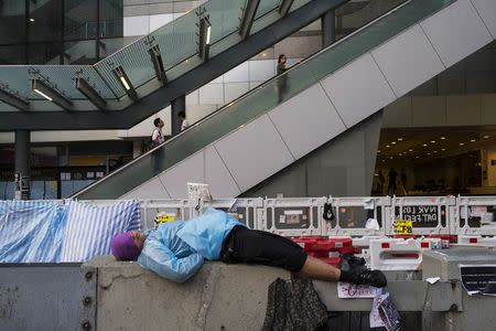 A protester of the Occupy Central movement, blocking the main road leading to the financial Central district in Hong Kong, sleeps on a divider as people travel onto a footbridge October 7, 2014. REUTERS/Tyrone Siu