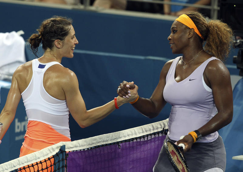 Serena Williams of the USA, right, shakes hands with Andrea Petkovic of Germany, left, after her 2nd round match at the Brisbane International tennis tournament in Brisbane, Australia, Tuesday, Dec. 31, 2013. Williams won the match 6-6, 6-4. (AP Photo/Tertius Pickard)