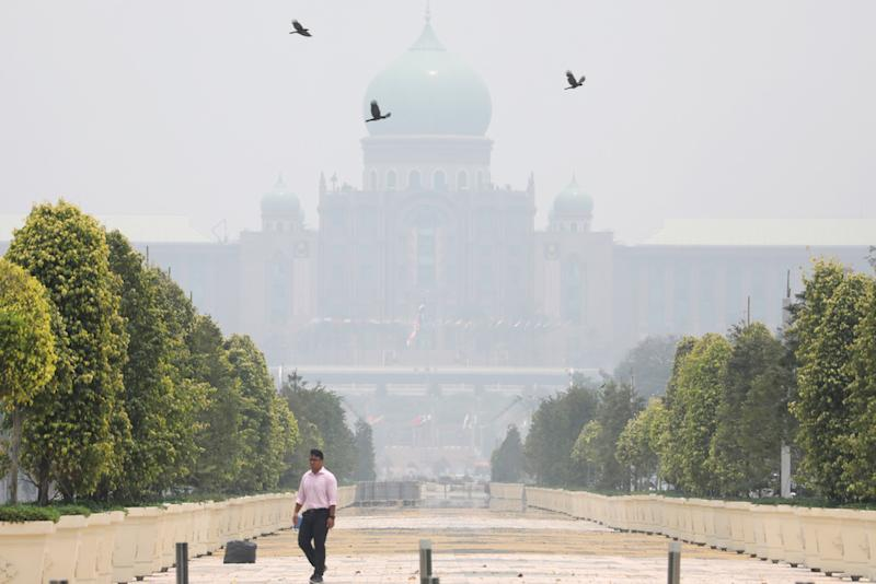 A man passes by the Prime Minister's Office, which is shrouded in haze, in Putrajaya September 23, 2019. — Reuters pic