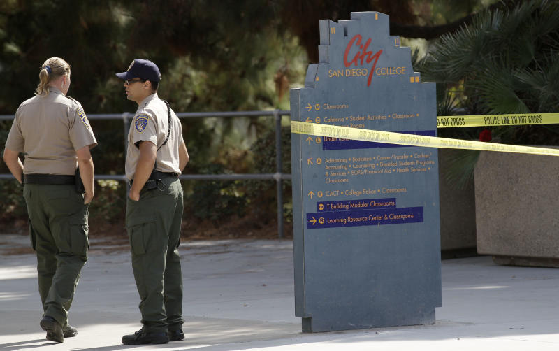 Campus police officials stand at the scene where the body of a woman was found in a bathroom Tuesday night on the campus of San Diego City College Wednesday, Oct. 13, 2010, in San Diego. School officials say the 19-year-old student found slain in the bathroom may have been the victim of domestic violence. (AP Photo/Gregory Bull)
