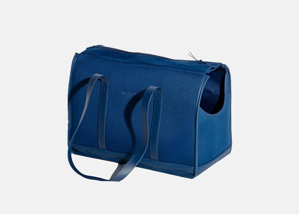 """<p>This minimalist carrier might look like a <a href=""""https://www.cntraveler.com/gallery/the-best-tote-bags-to-bring-on-a-flight?mbid=synd_yahoo_rss"""" rel=""""nofollow noopener"""" target=""""_blank"""" data-ylk=""""slk:tote bag"""" class=""""link rapid-noclick-resp"""">tote bag</a>, but it's made of weather-resistant material, and features a cushioned base, soft straps, and head scoop to make sure your pet always has the window seat. Its sturdy, reinforced structure also ensures the carrier will never lose its shape and comes with a handy internal pocket for any essentials (read: treats), as well as a collar attachment.</p> <p><strong>Buy now:</strong> <a href=""""https://fave.co/3hlINgz"""" rel=""""nofollow noopener"""" target=""""_blank"""" data-ylk=""""slk:$180, wildone.com"""" class=""""link rapid-noclick-resp"""">$180, wildone.com</a></p>"""