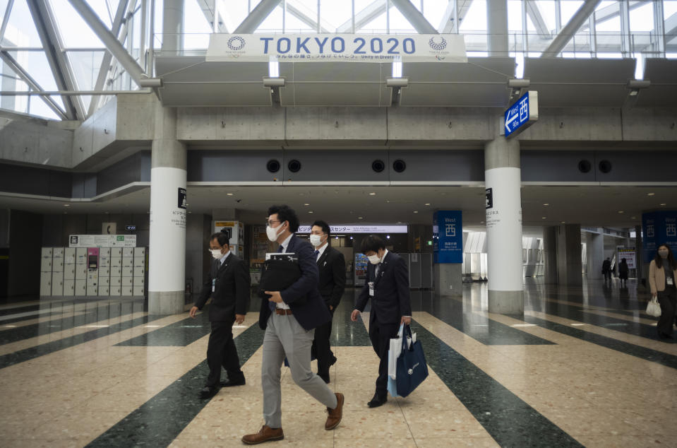 People walk under a banner promoting the postponed Tokyo 2020 Olympic and Paralympic Games at the Tokyo International Exhibition Center, in Tokyo Thursday, April 8, 2021. The exhibition center, also known as Tokyo Big Sight, is a planned venue for the Tokyo 2020, rescheduled to start in July 2021. Many preparations are still up in the air as organizers try to figure out how to hold the postponed games in the middle of a pandemic. (AP Photo/Hiro Komae)