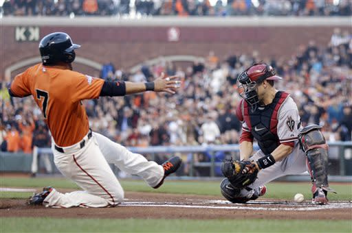 San Francisco Giants' Gregor Blanco scores against Arizona Diamondbacks catcher Miguel Montero on a double from Buster Posey during the first inning of a baseball game Friday, July 19, 2013, in San Francisco. (AP Photo/Marcio Jose Sanchez)