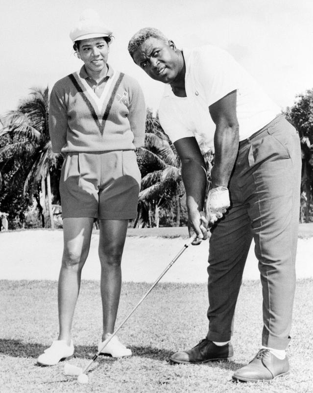 """FILE - In this Feb. 23, 1962 file photo shows Althea Gibson, former amateur tennis champion, and Jackie Robinson at the North-South Tournament at the Miami Springs course. When the US Open begins this week, she will have a statue unveiled in her honor. Says tennis great Billie Jean King: """"She's our Jackie Robinson of tennis."""" (AP Photo)"""