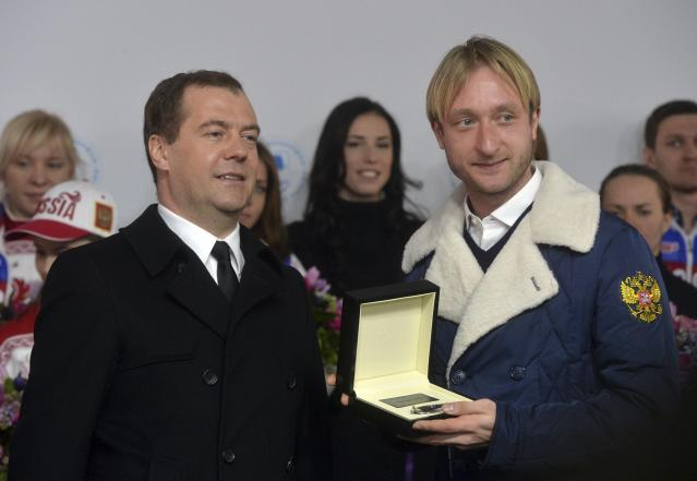 Russia's Prime Minister Dmitry Medvedev and figure skating gold medal winner Evgeni Plushenko (R) attend a ceremony to present automobiles to the Sochi 2014 Winter Olympics prize-holders representing Russia, by the Kremlin wall in central Moscow, February 27, 2014. REUTERS/Artem Zhitenev/RIA Novosti/Pool (RUSSIA - Tags: POLITICS SPORT OLYMPICS) ATTENTION EDITORS - THIS IMAGE HAS BEEN SUPPLIED BY A THIRD PARTY. IT IS DISTRIBUTED, EXACTLY AS RECEIVED BY REUTERS, AS A SERVICE TO CLIENTS
